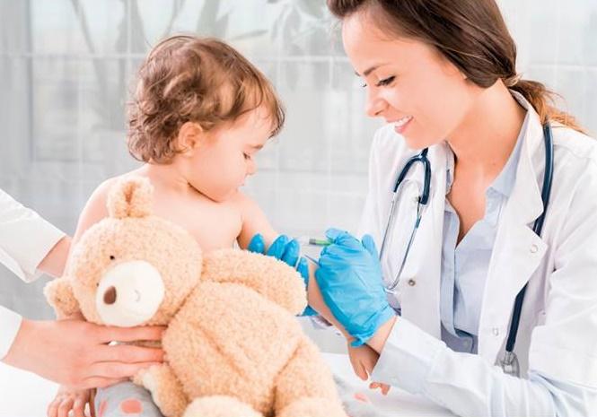 Lekarka szczepi małe dziecko, które trzyma misia