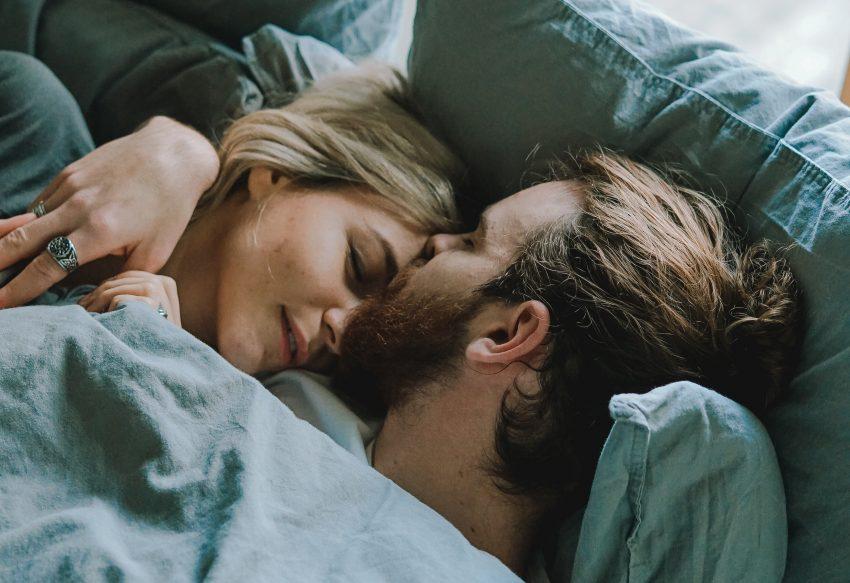 para leżąca w łóku, on ją całuje w czoło