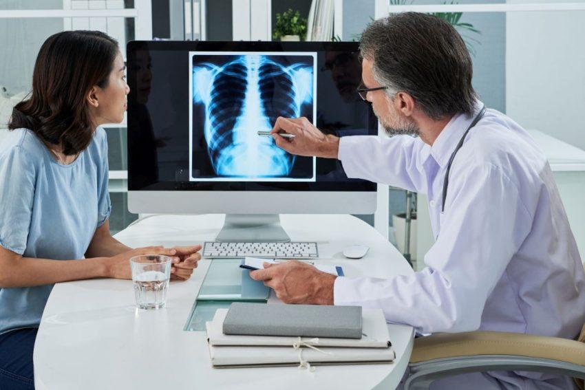 Lekarz pokazuje na rentgen i tłumaczy pacjentce przyczyny zapalenia płuc