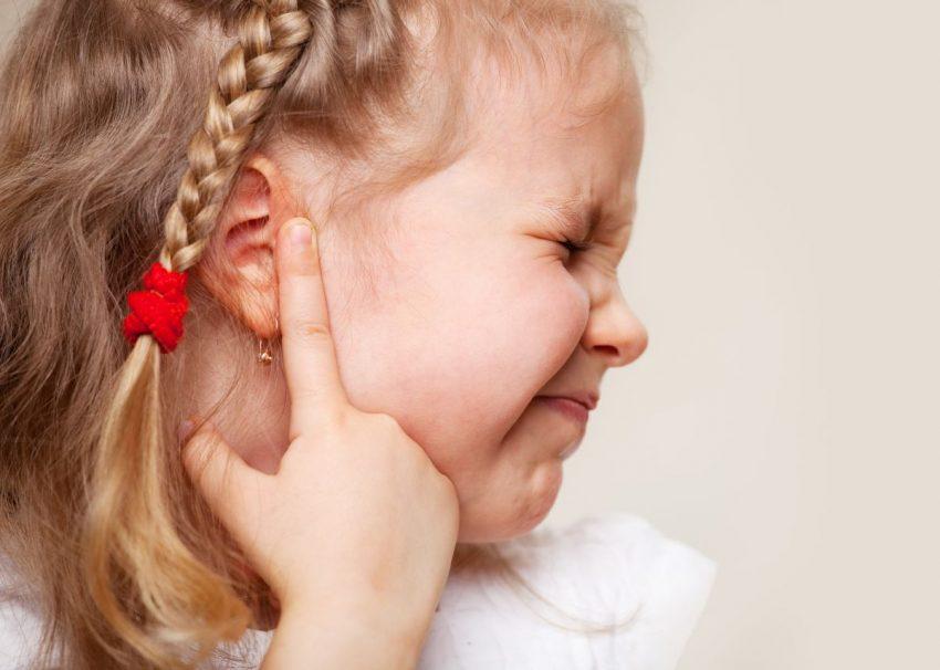 Dziewczynka trzyma palec przy uchu z powodu zapalenia ucha