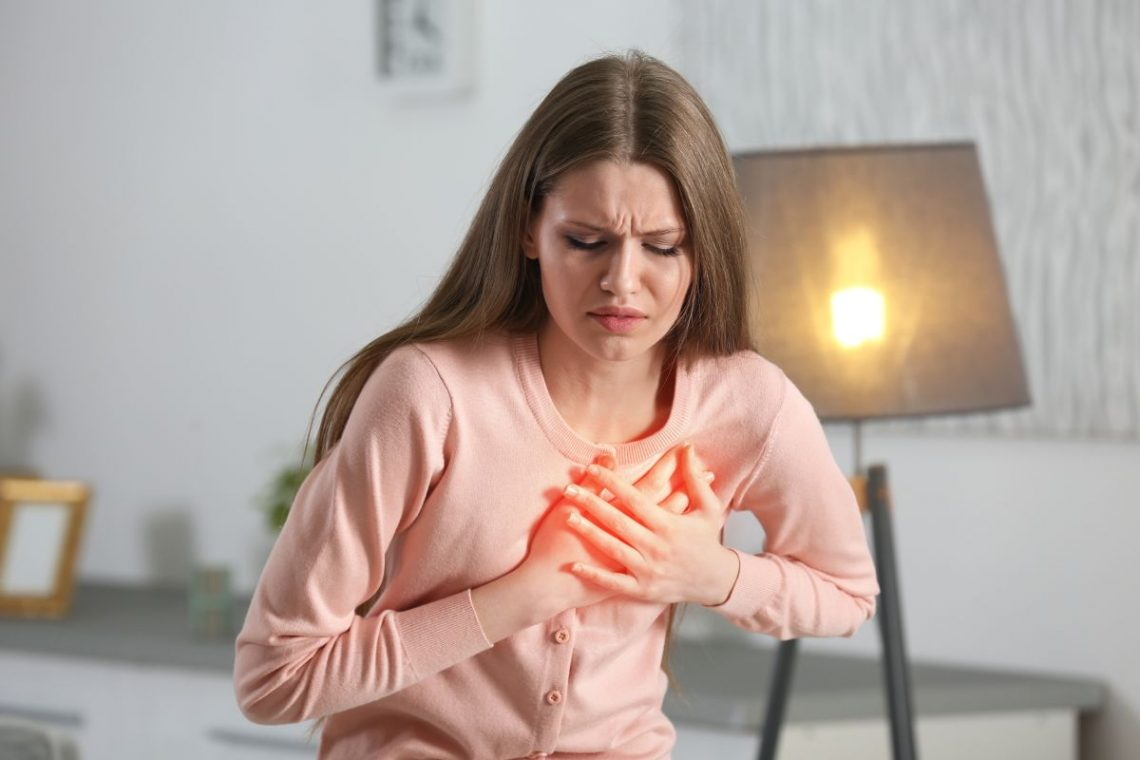 Kobieta trzyma się za serce, bo ma zawał serca
