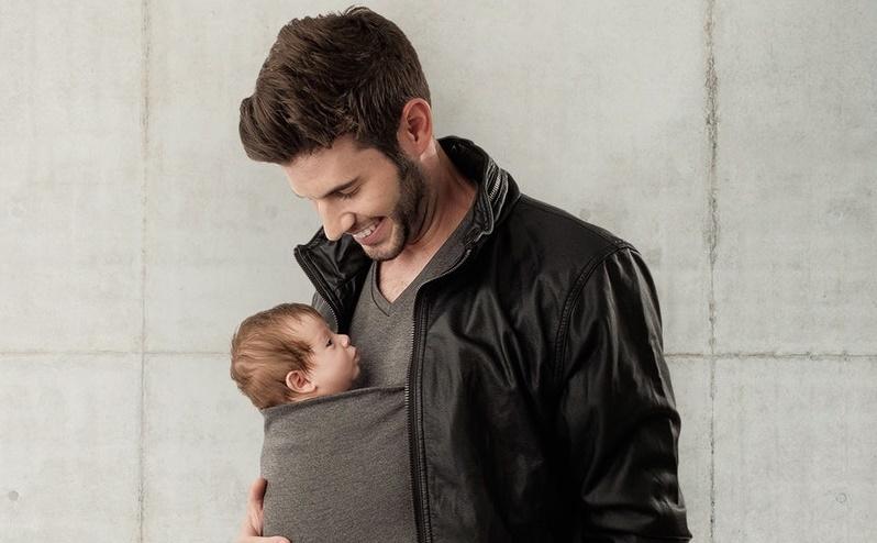 mężczyzna w koszulce z kieszenią na piersi, w której siedzi dziecko
