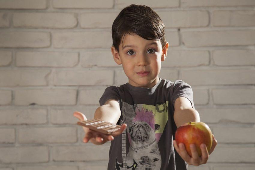 Chłopiec trzyma jedzenie, którego nie może jeść z powodu alergii pokarmowej