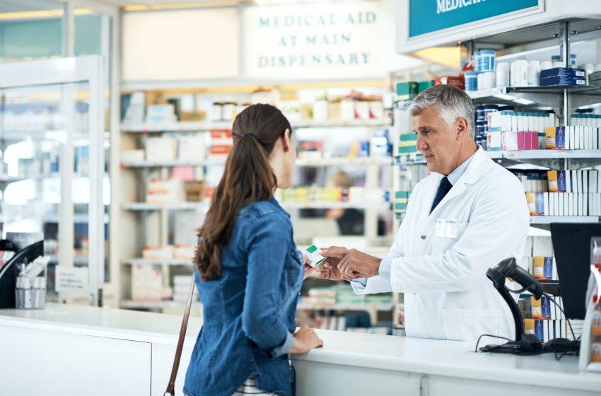 Kobieta w aptece rozmawia z farmaceutą