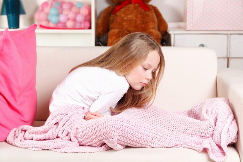 Dziewczynka z bólem brzucha siedzi pod kocem