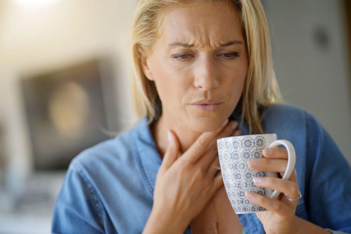 Kobieta trzymająca się za szyję z powodu bólu gardła