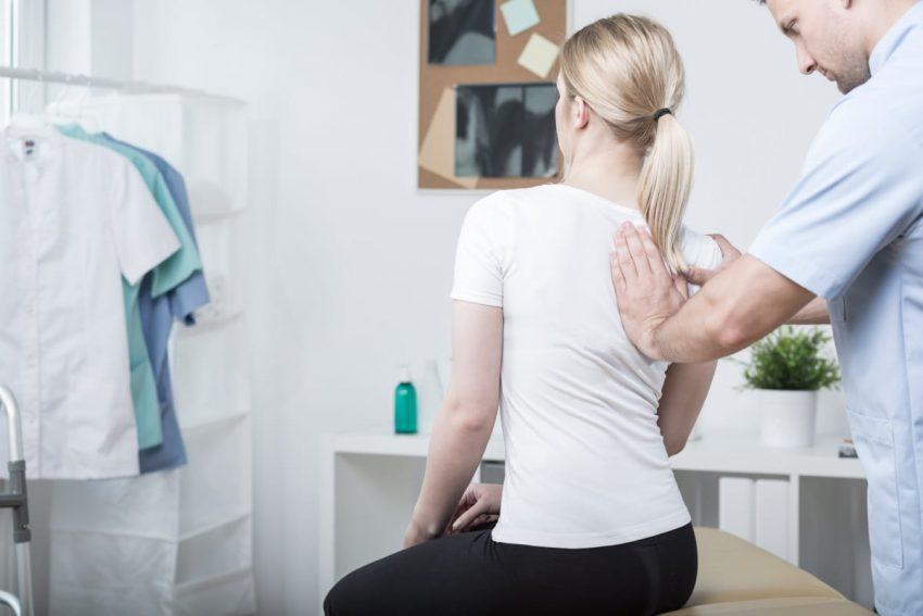 Masażysta masuje kobietę z bólem kręgosłupa pomiędzy łopatkami