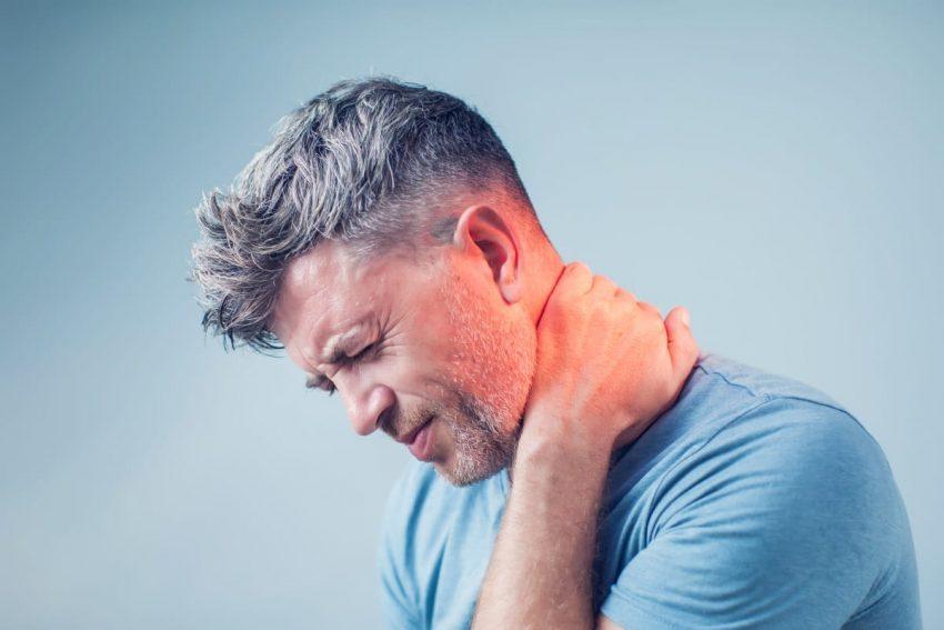 Mężczyzna zgina głowę z powodu bólu kręgosłupa szyjnego