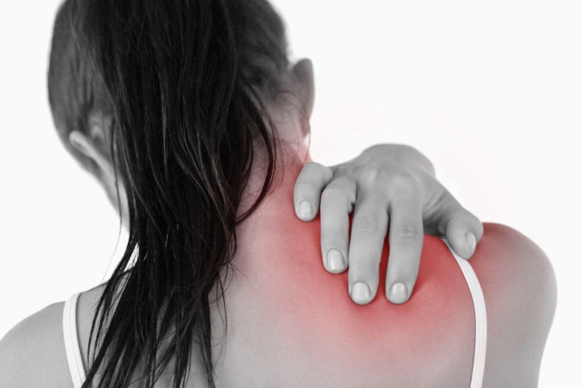 Kobieta trzymająca się za plecy między łopatkami z powodu bólu łopatek
