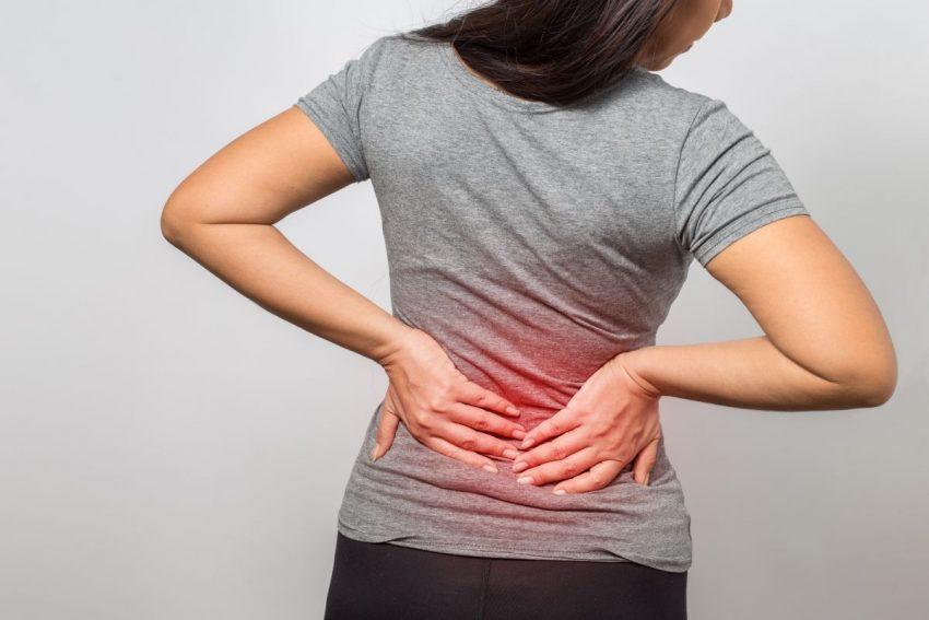 Kobieta trzymająca się za plecy na dole z powodu bólu pleców