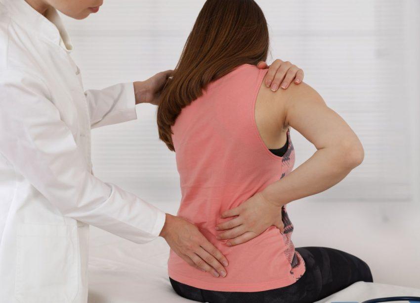 Kobieta trzymająca się za odcinek lędźwiowy pleców z powodu bólu pleców