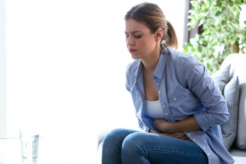 Kobieta trzyma się z brzuch z powodu bólu w dole brzucha