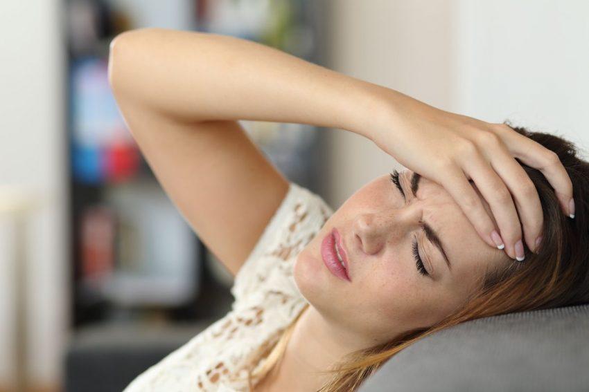 Kobieta z bólem z tyłu głowy leży na kanapie