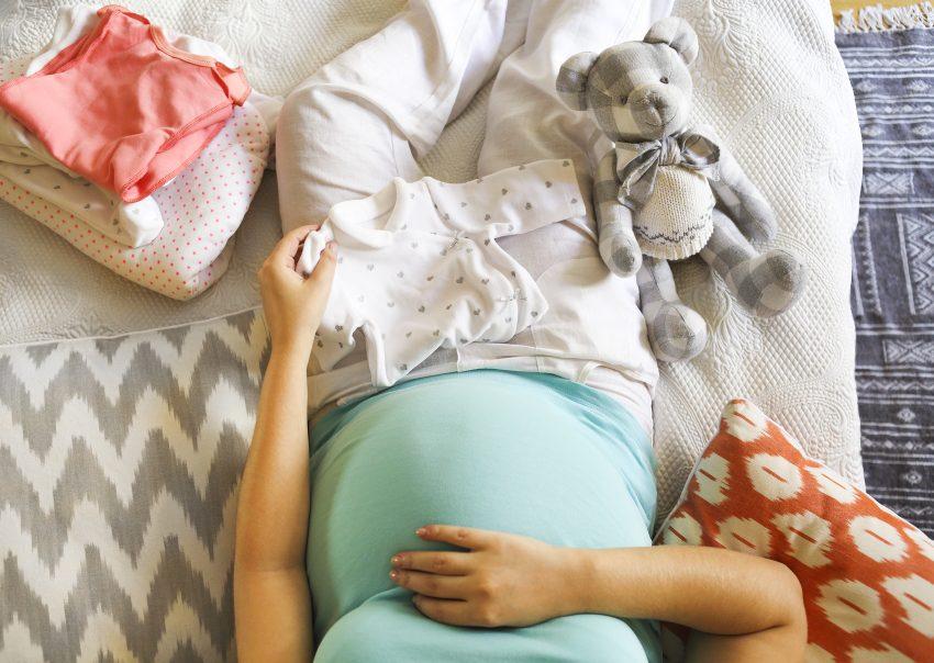 Kobieta w ciąży, która układa dziecięce ubranka