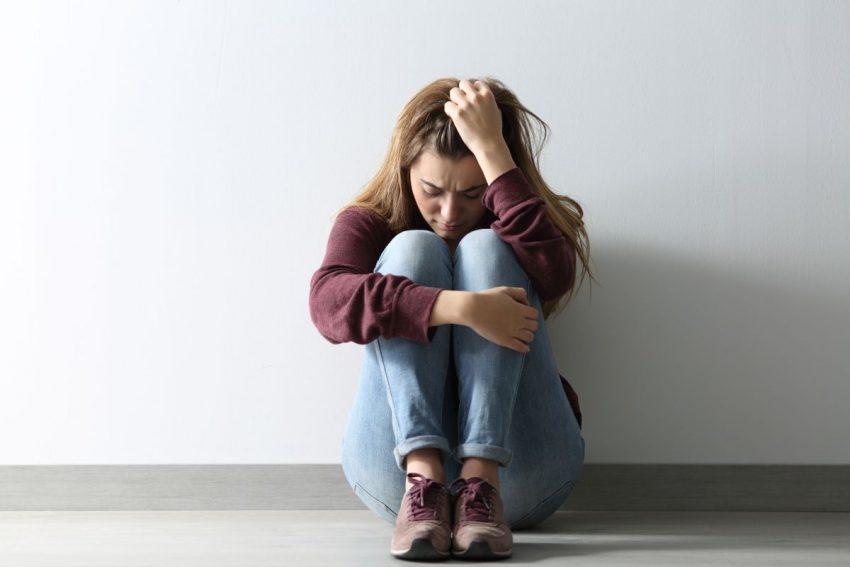 Kobieta z depresją siedzi oparta o ścianę