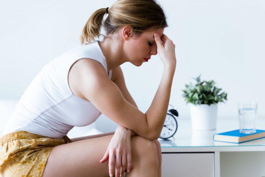 Kobieta cierpiąca na depresję trzyma się za głowę