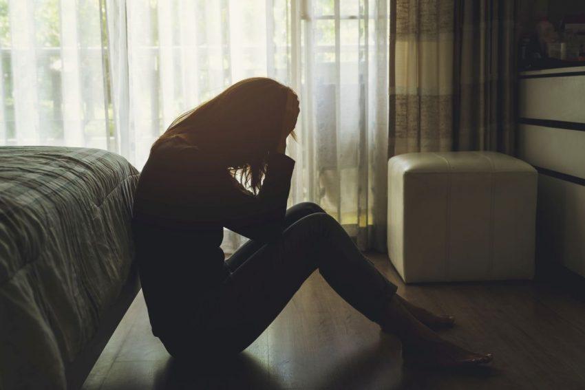 Zdesperowana kobieta siedzi przy łóżku, w ciemnym pokoju
