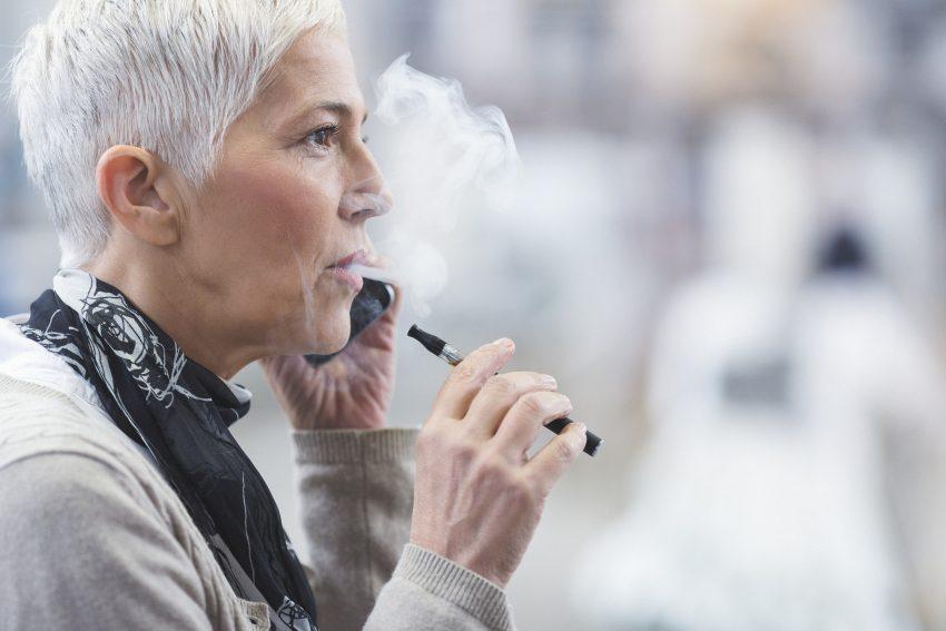 Kobieta trzyma w ręku e-papierosa
