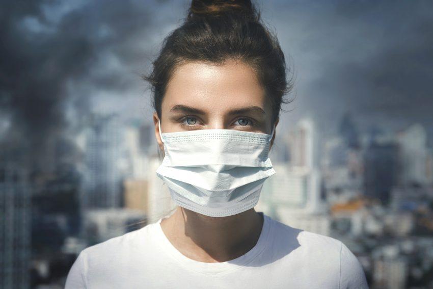 Kobieta w masce, za nią miasto w smogu