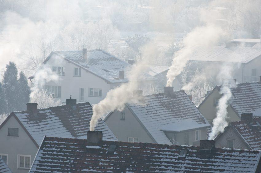 dachy domów z kominami, z których leci dym