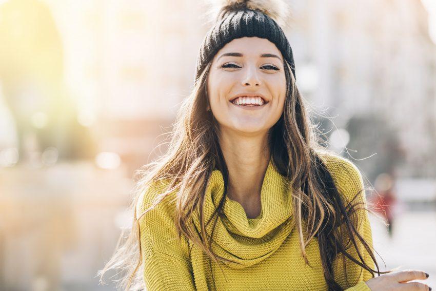 uśmiechnięta kobieta w czapce zimowej i żółtym golfie