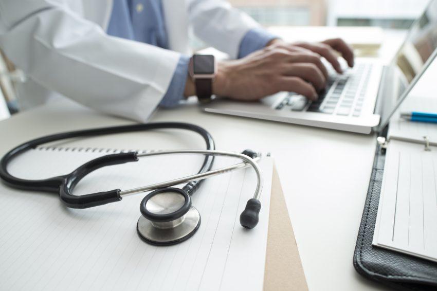 lekarz pisze na komputerze obok leży stetoskop