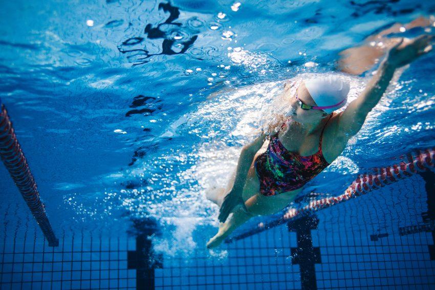 kobieta płynie kraulem na sportwym basenie, ubrana w kolorowy, jednoczęśowy kostium, czepek oraz okulary do pływania. Zdjecie zrobione spod wody.