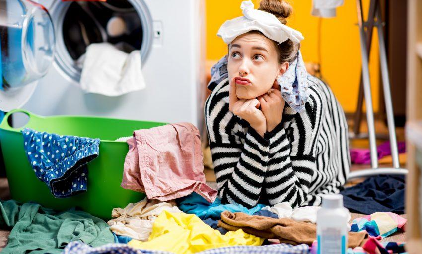 Kobieta podpiera się łokciami i myśłi na podłodze w łazience. Wszędzie jest rozrzucone pranie.