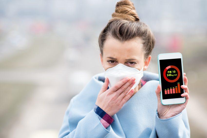 Kobieta w masce pokazuje na telefonie poziom stężenia pyłu smogowego