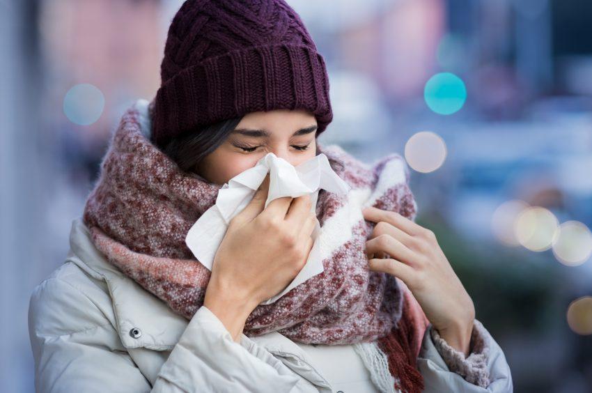 kobieta w czapce i szaliku wydmuchuje nos w chusteczkę