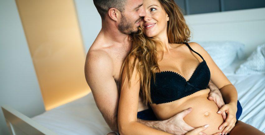 para siedzi na łóżko, ona w ciąży, on obejmuje ją od tyłu