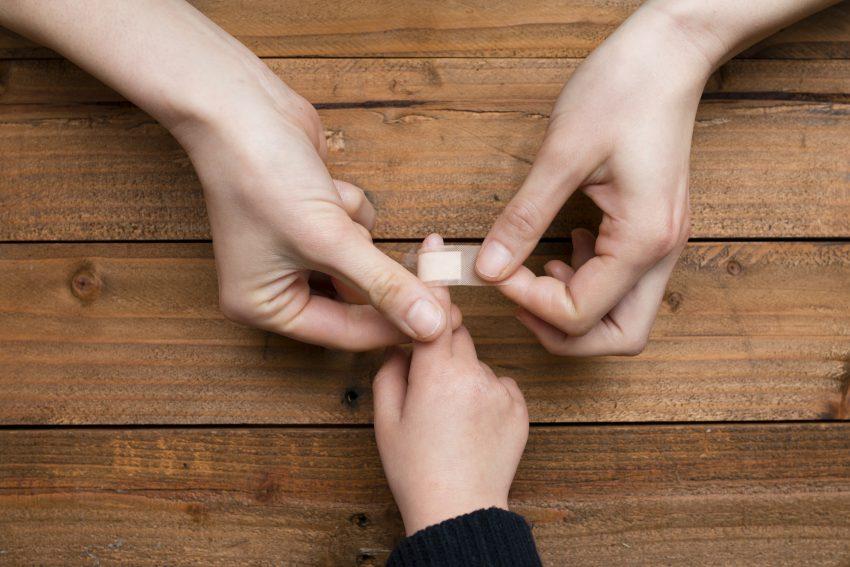 Mama zakleja plaster dziekcu. Na zdjeciu widoczne dłonie na drewnianym stole