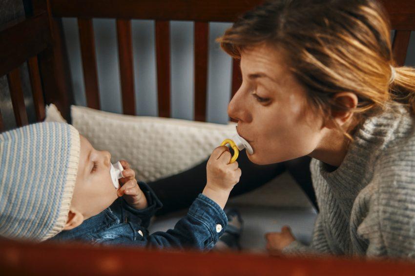 matka z dzieckiem w drewnianym łóżeczku, dziecko wkłada smoczka mamie do buzi. Sam też ma smoczek w buzi