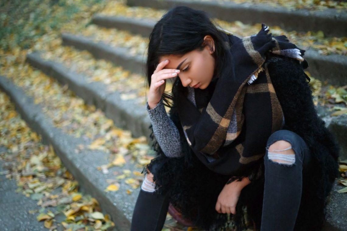 Kobieta z depresją siedzi na schodach