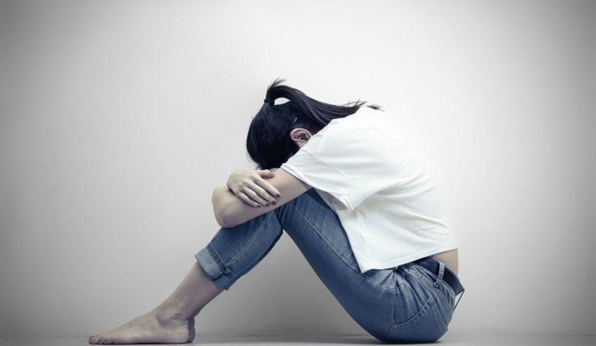 Smutna kobieta z depresją siedzi obejmując swoje kolana i płacząc