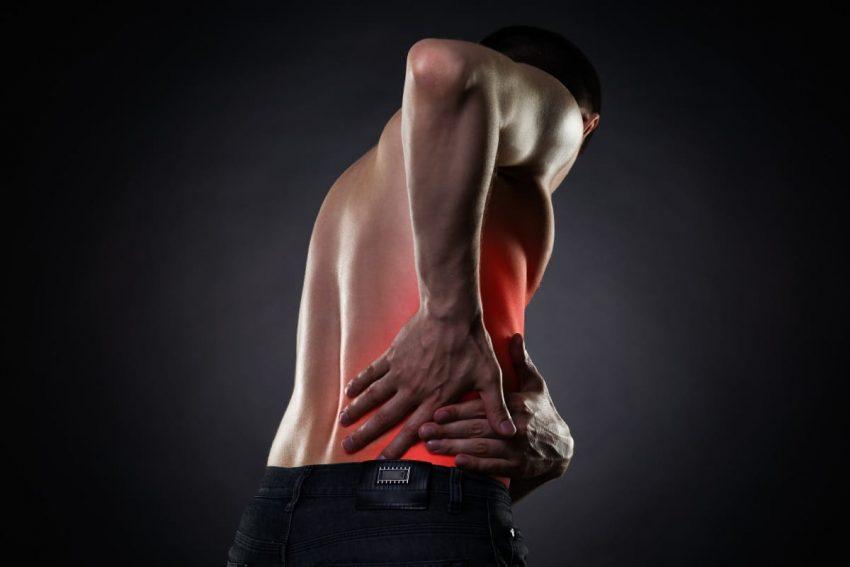 Mężczyzna z kamicą nerkową ugina się z powodu wielkiego bólu