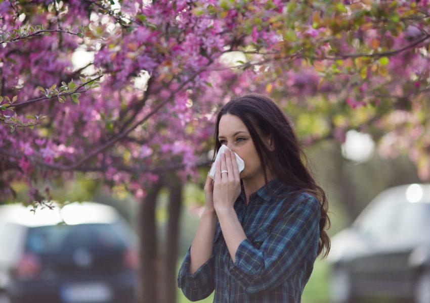 Kobieta z katarem siennym dmucha nos