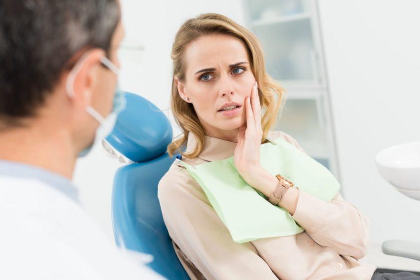 Kobieta u dentysty czeka na leczenie kanałowe