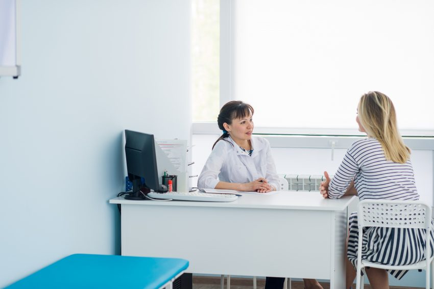 Kobieta rozmawia z lekarzem w gabinecie