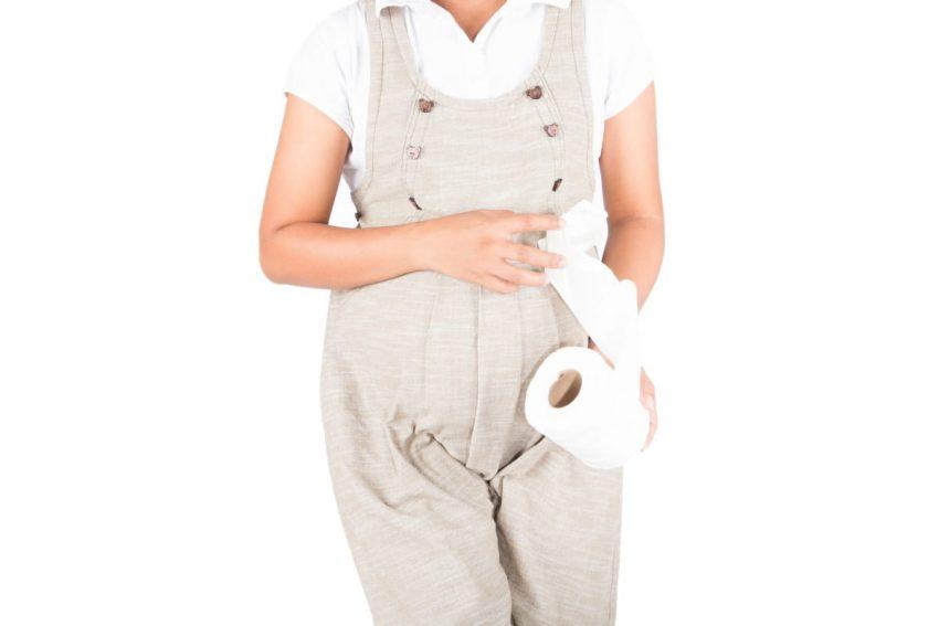 Kobieta w ciąży trzyma papier, bo ma problem z nietrzymaniem moczu