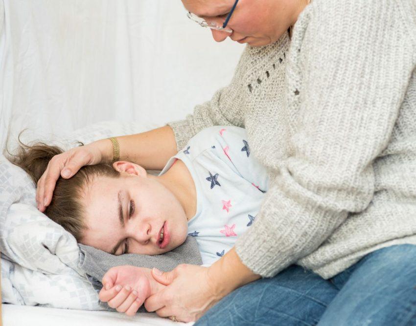 Dziewczynka leży w łóżku po tym, jak miała objawy padaczki