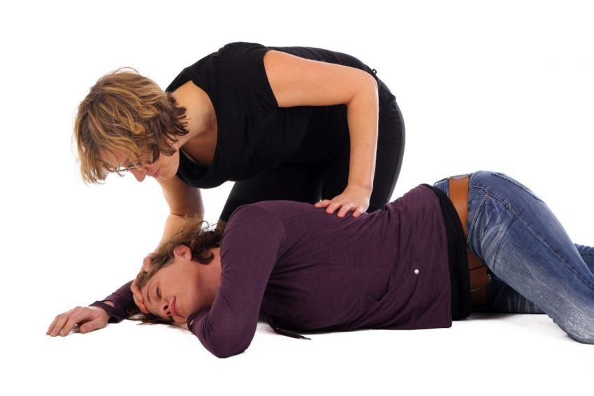 Kobieta pochyla się nad koleżanką, która miała napad padaczki skroniowej