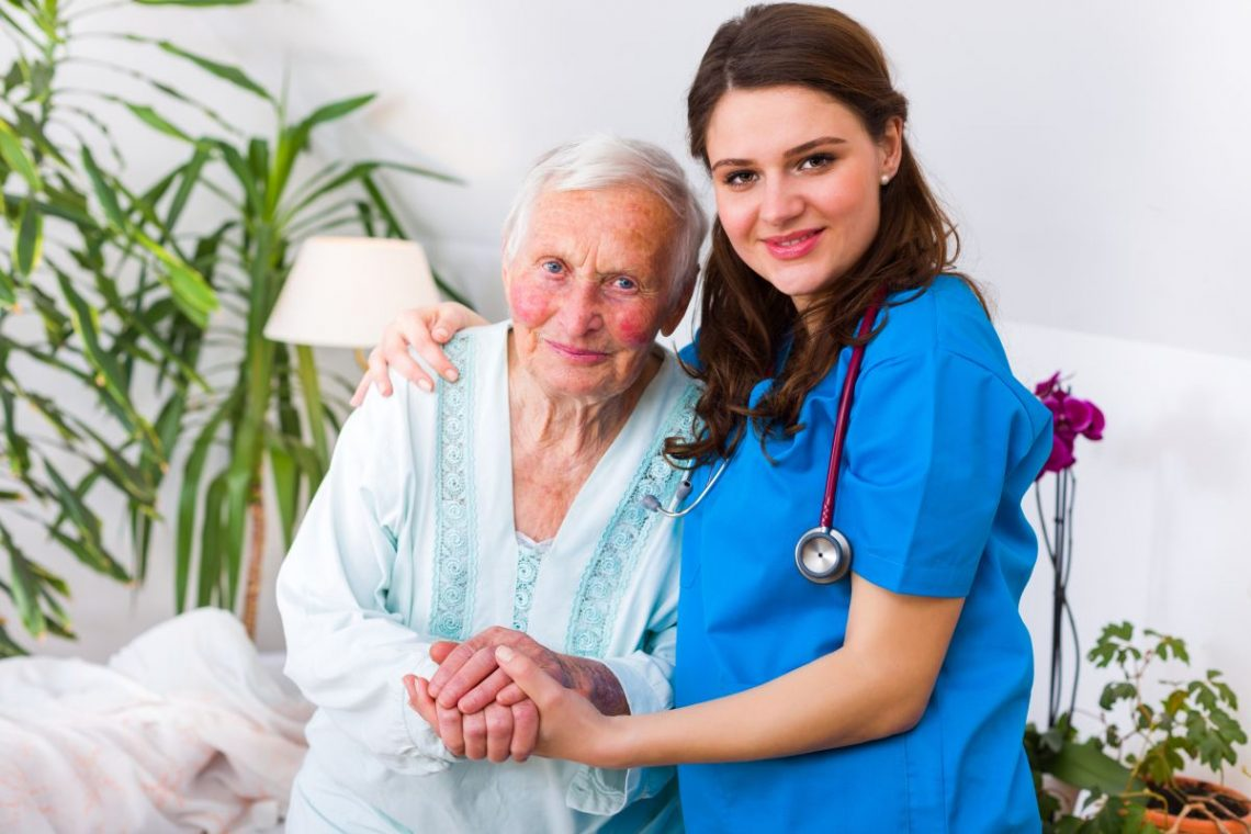 Starsza kobieta z chorobą Parkinsona w towarzystwie pielęgniarki
