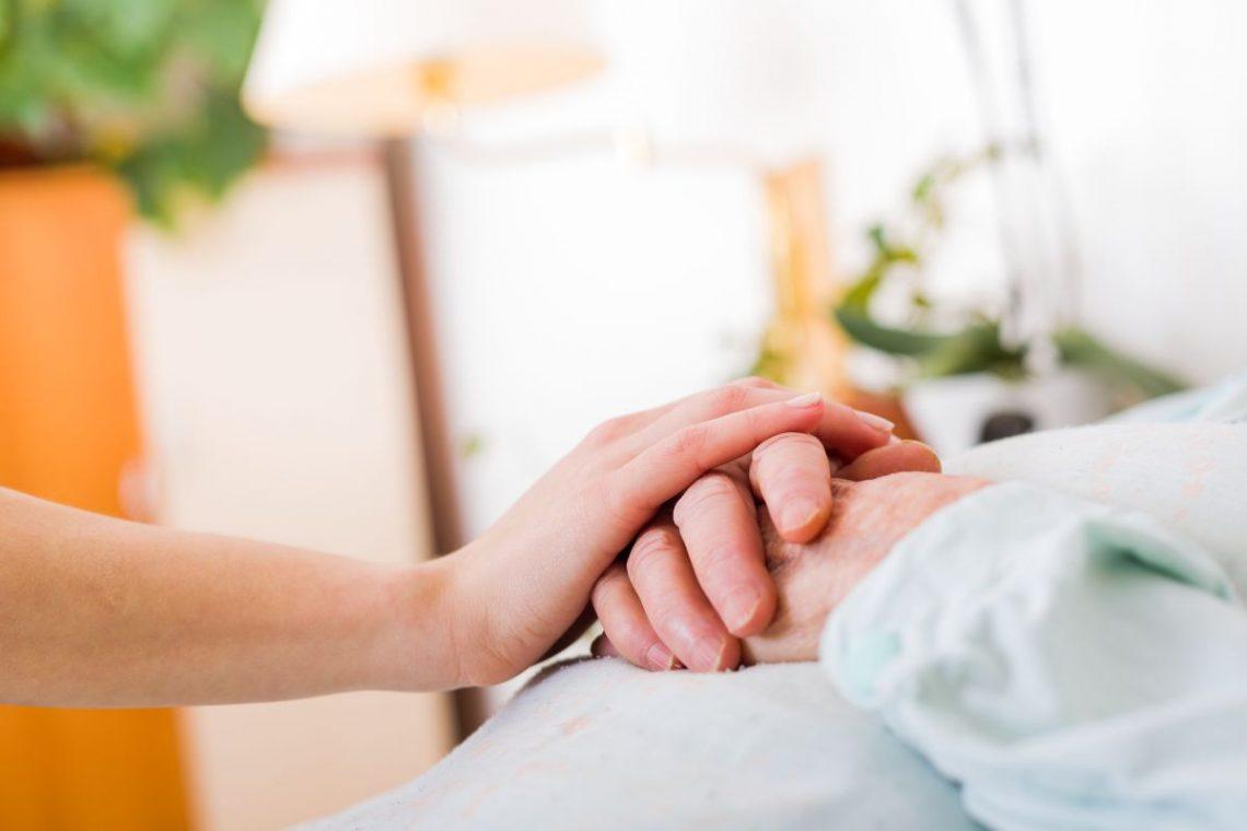 Osoba odwiedzająca osobę chorą na Parkinsona trzyma dłoń na jej dłoniach