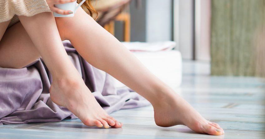 gołe kobiece nogi i kubek kawy