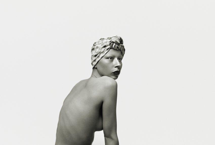 Zuzanna Bartoszek w obiektywie Tomasza Wirskiego. Zdjęcie nagich pleców, modelka patrzy w prawo. Ma pomalowane ustai chustkę na głowie. Jest naga. Zdjęcie do pasa, czarno-białe