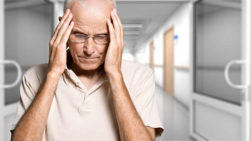 Mężczyzna trzyma się za głowę z powodu objawów udaru mózgu