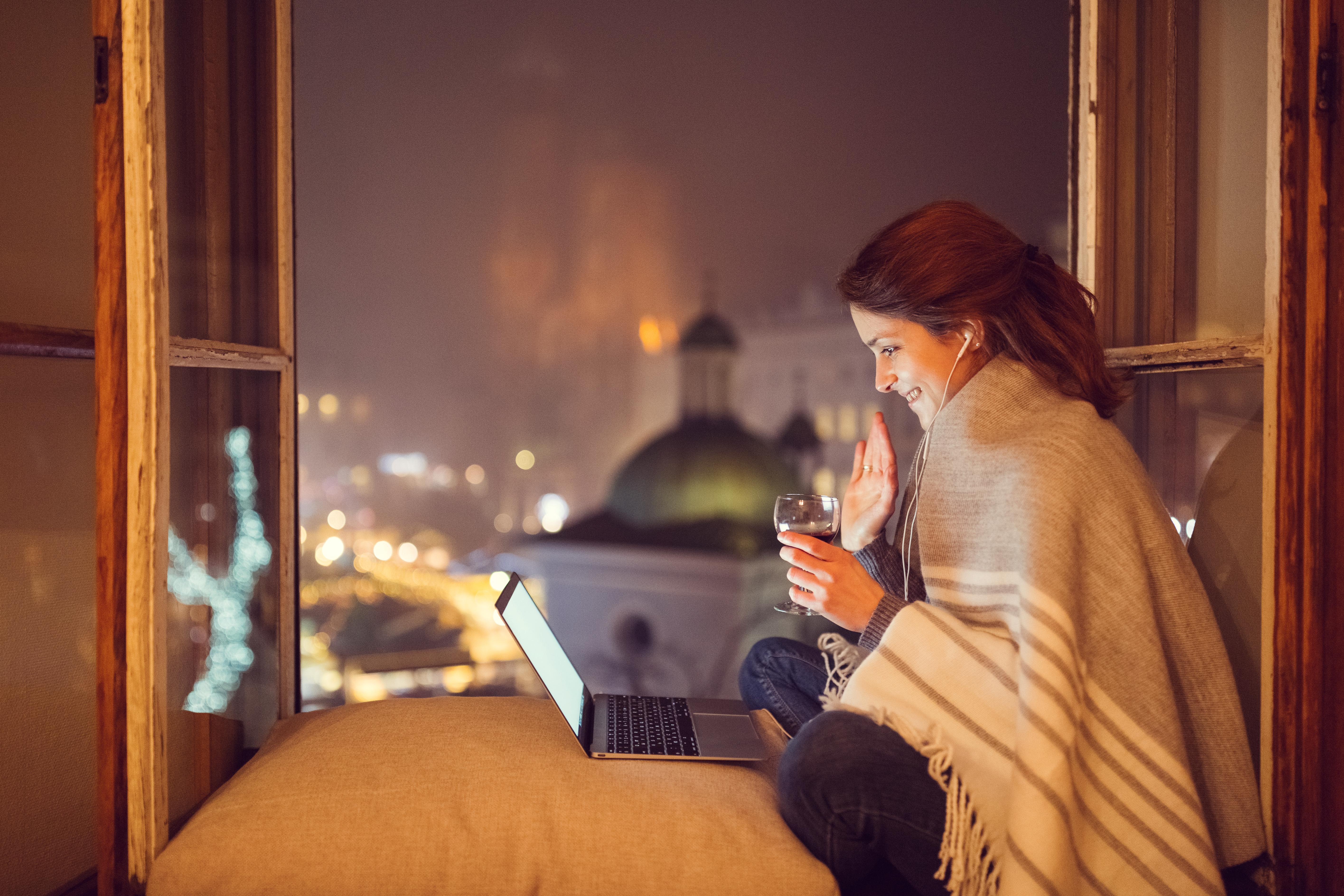 dziewczyna siedząca przy otwartm oknie, przed nią stoi laptop, okrywa się kocem
