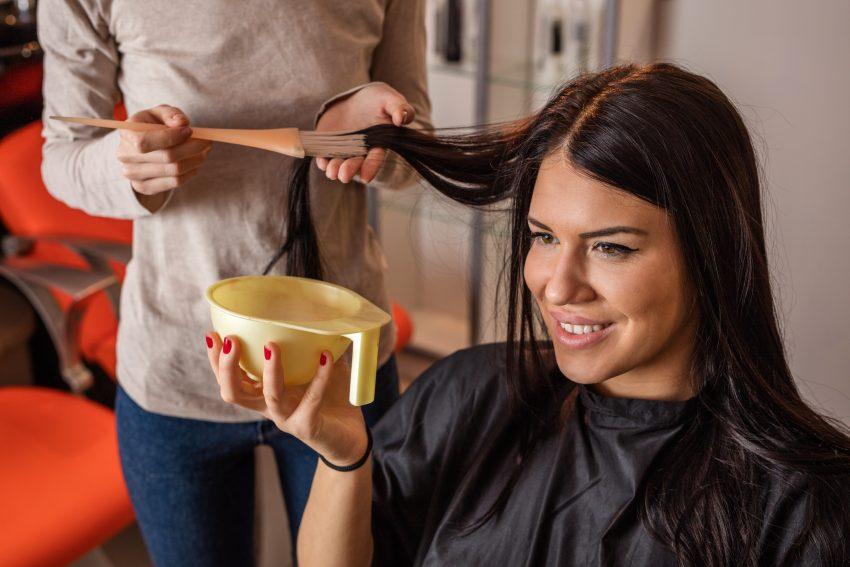 Kobieta podczas farmowania włosów, trzymająca pojemnik na farbę