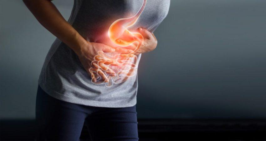 Kobieta uciska brzuch z powodu objawów wrzodów żołądka